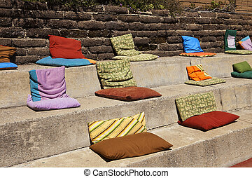 Pillows On Concrete Steps - Soft, colorful cushy pillows on...