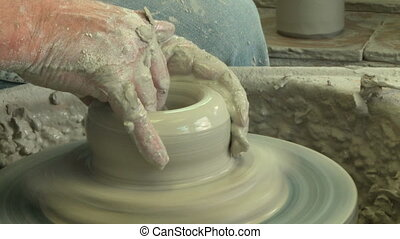 Potter shaping a tall vase 3 - Potter shaping a vase on the...
