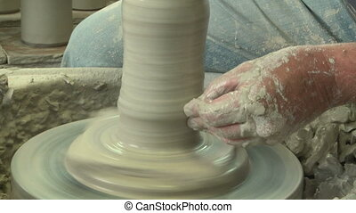 Potter shaping top of vase 4 - Potter shaping a vase on the...