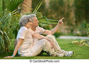 Old couple on grass - Loving elder couple sitting on a...