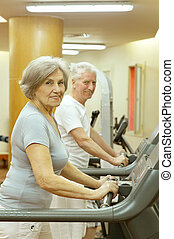 senior couple exercising in gym - active cute senior couple...