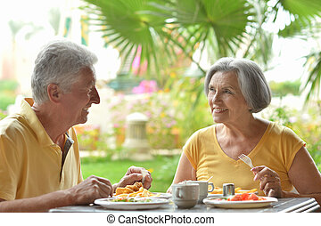 Senior couple eat outside at the resort during vacation