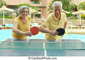 Elderly couple playing ping pong at hotel yard