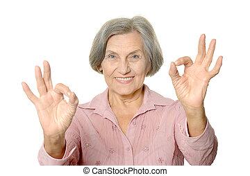 Senior woman show ok on white background