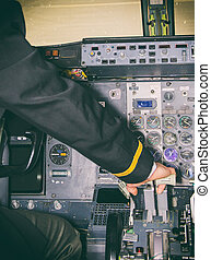 Rear view of pilot in aircraft cabin.
