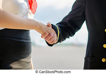 Pilot and stewardess shaking hands on airfield background