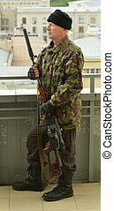 Armed senior man with weapon aiming from abandoned building