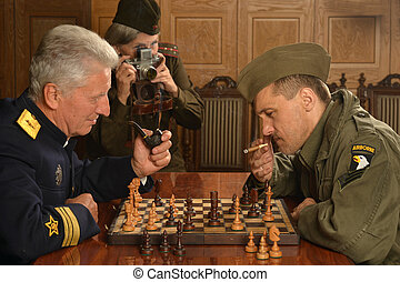 Military mature general playing chess with soldier -...