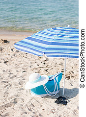 Beach Scene - Turquoise bag and white hat on the beach.