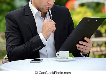 Cafe - Young businessman drinking coffee while sitting in a...