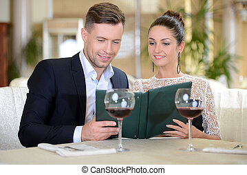 Restaurant - Young elegant couple drinking wine sitting in a...