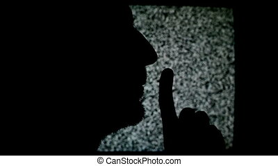 Man making Shhh sign with finger. Silhouette of unshaven...
