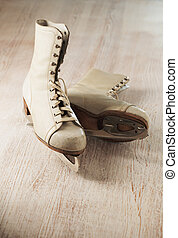 Old skates - Old and worn womens white ice skates on wooden...