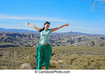 Happy woman open arms stand at mountain - Young happy woman...