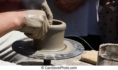 Potters hands working clay on potters wheel