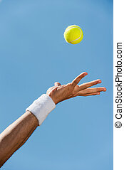 Serving ball. Close-up of male hand in wristband throwing...