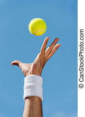 Serving tennis ball. Close-up of male hand in wristband...