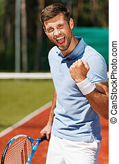 I won! Happy young man in polo shirt holding tennis racket...