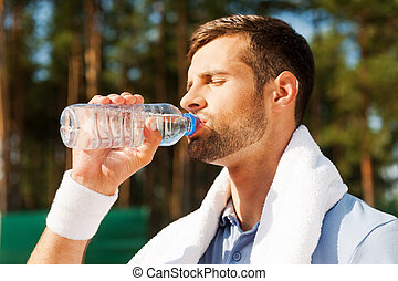 Getting refreshed after game Side view of thirsty young man...