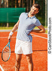 Feeling pain in his back. Close-up of tennis player touching...