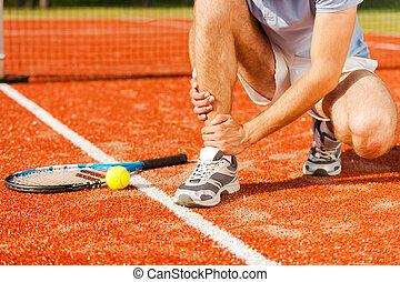 Sports injury. Close-up of tennis player touching his leg...