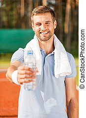 Drink some water Happy young man in polo shirt and towel on...