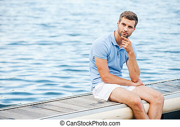 Handsome day dreamer. Thoughtful young man holding hand on chin and looking away while sitting at the riverbank