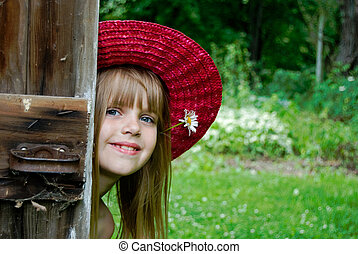 Country Style - Little girl peeking around an old wooden...