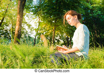 young beautiful girl sitting in a park and writing in a...