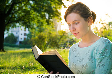 young beautiful girl reading a book in the park