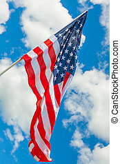 Hanging USA flag with white clouds on background