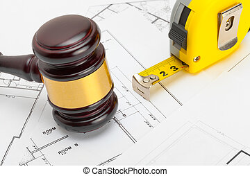 Wooden judge gavel with measure tape above construction...