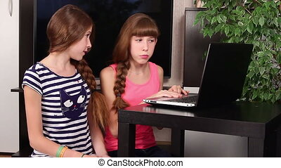 children with laptop - Two happy girls-twins with laptop