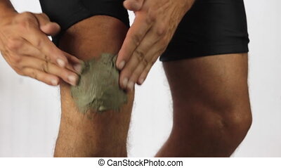 knee pain - Male runner using therapeutic clay on his knee