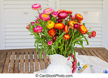 Bouquet of Everlasting flowers bouquet in vase on wooden...