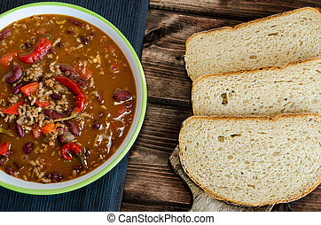Chilli con carne with fresh bread on wood
