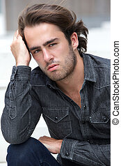 Male fashion model sitting outside - Close up portrait of a...