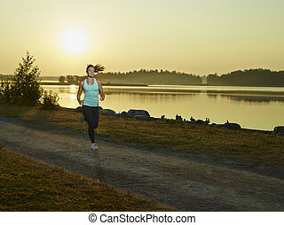 Sporty fitness woman runs in the park early in the morning,...