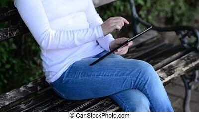 Woman holds and taps digital tablet computer on a wooden...