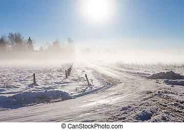 winter landscape at fog  with road near farm