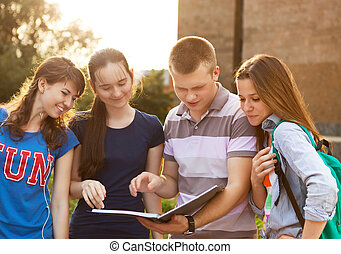Group of students or teenagers with notebooks outdoors in...