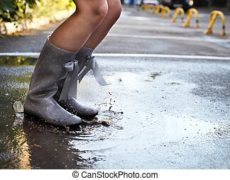 Woman wearing grey polka dots rain boots jumping into a puddle