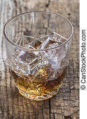 Crystal clear luxury glass with liquor and ice cubes
