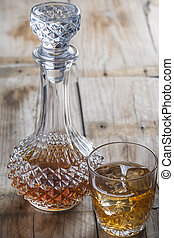 Crystal clear luxury glass bottle with liquor and a glass to...