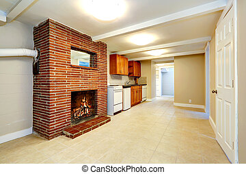 Empty basement room with brick fireplace