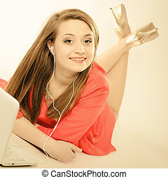 Girl with earphones and computer listening to music