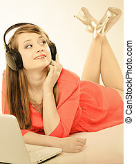 Girl with headphones and computer listening to music