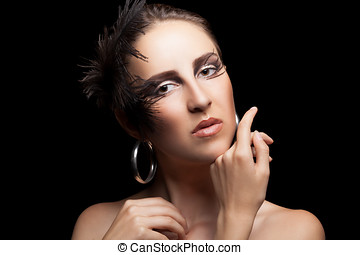 Woman with feathers and gothic make up isolated on black...