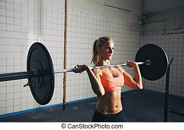 Strong woman lifting weights in crossfit gym - Fitness woman...