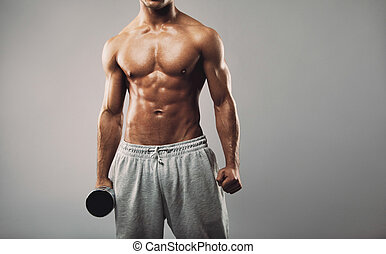 Shirtless young muscular man with dumbbell - Cropped image...